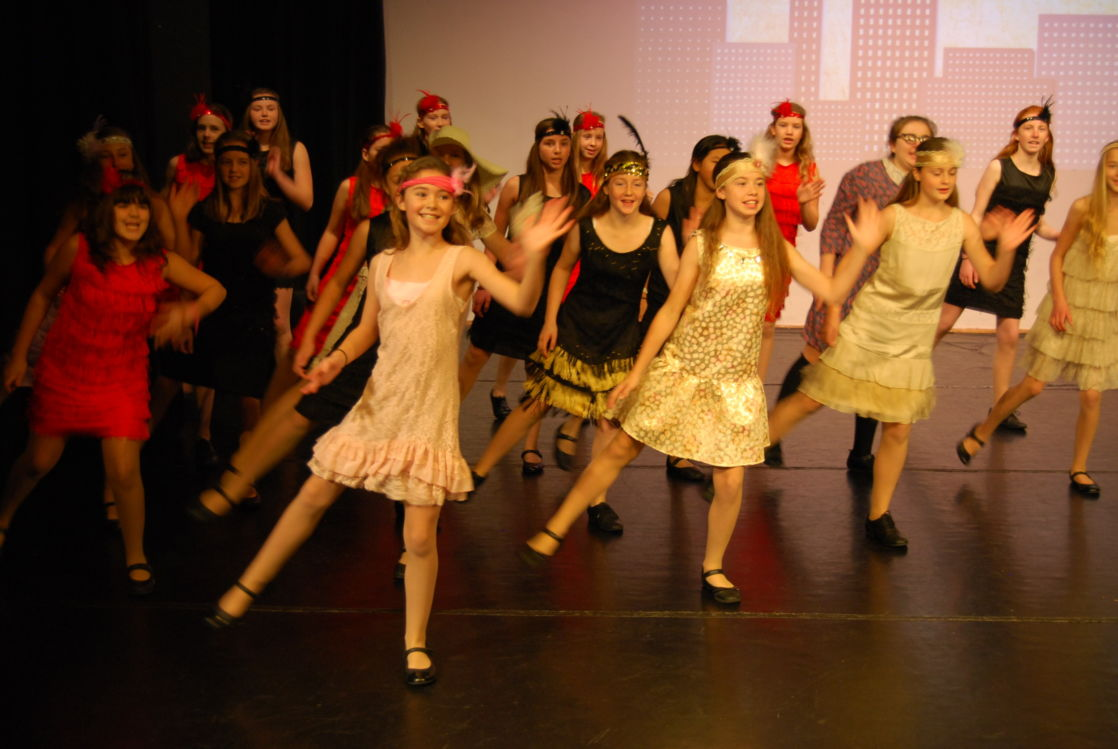 wycliffe girls in costumes dancing onstage