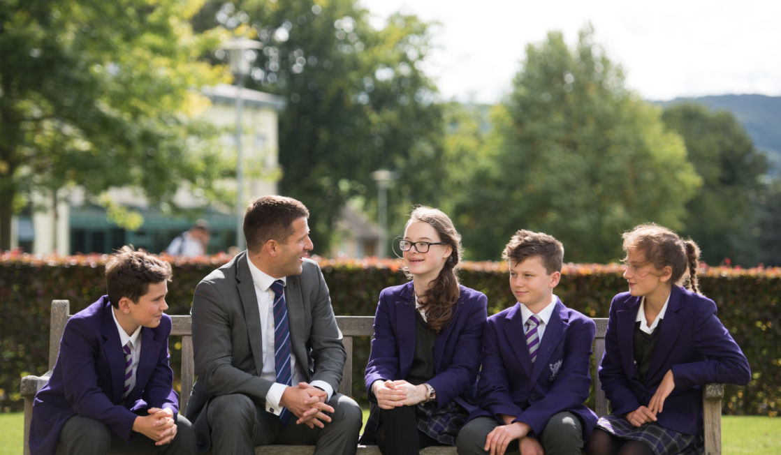 wycliffe kids and teacher sitting on a bench outdoors