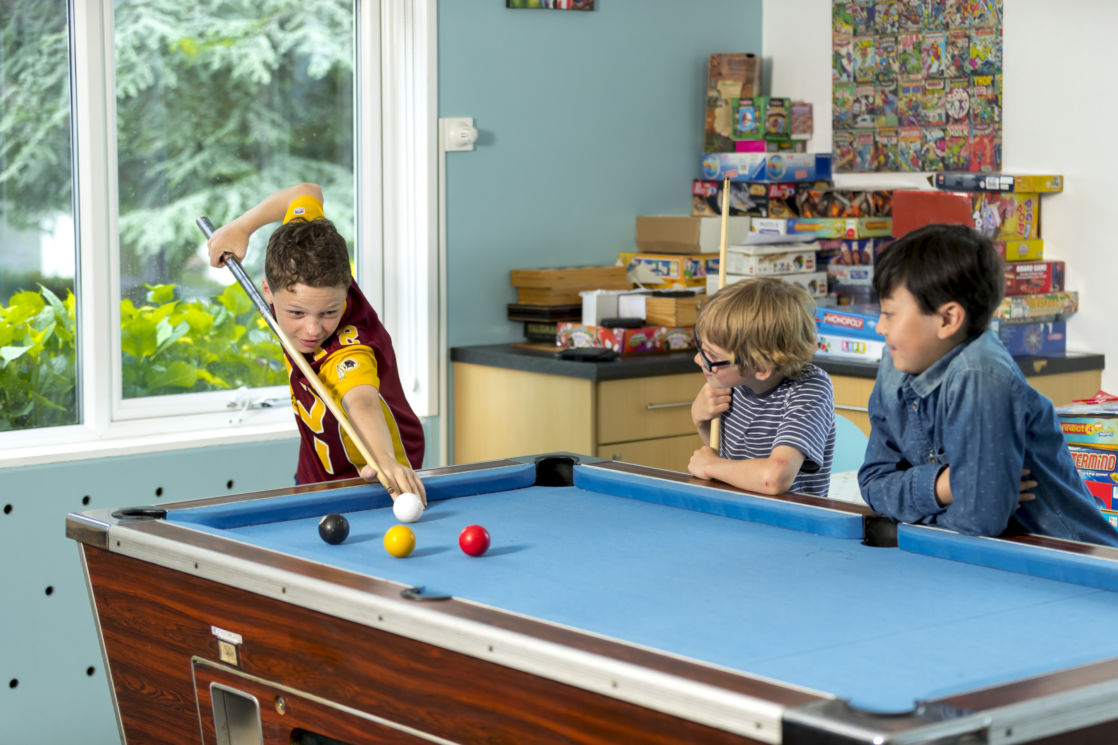 Prep boys playing pool in their boarding house