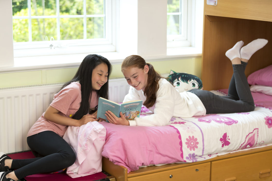wycliffe girls reading a book in their dorm