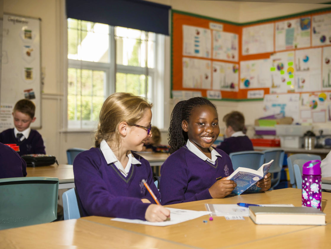 wycliffe girls smiling and reading in class