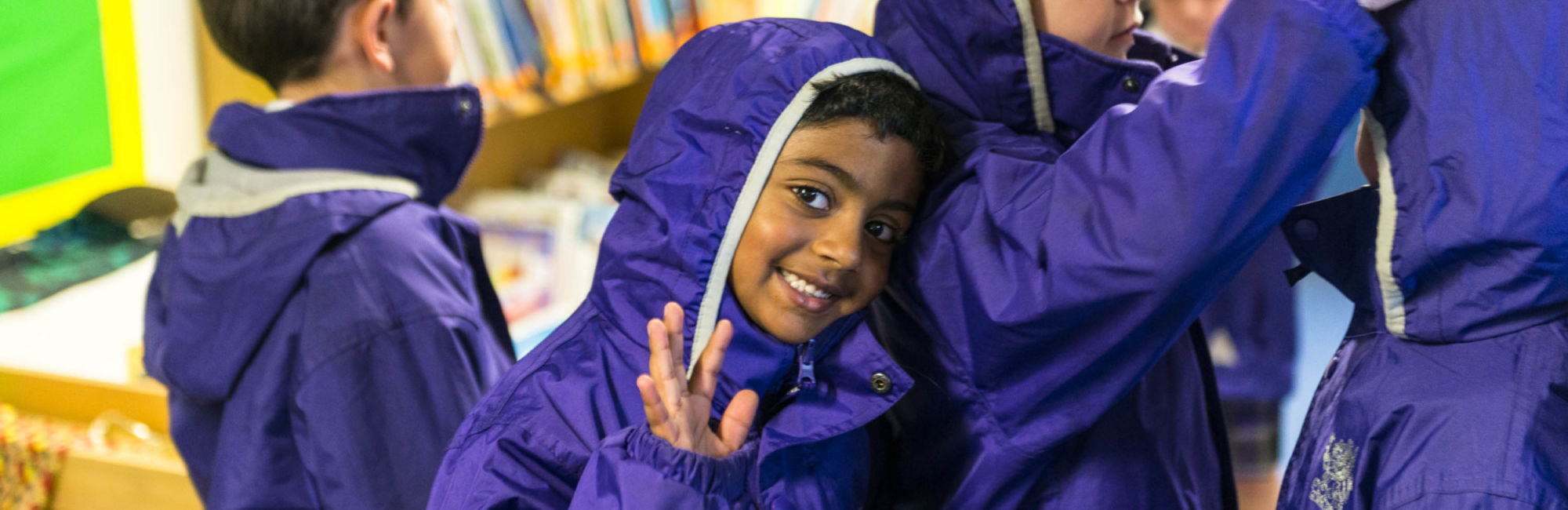 wycliffe nursery pupils smiling and putting on trenchcoats