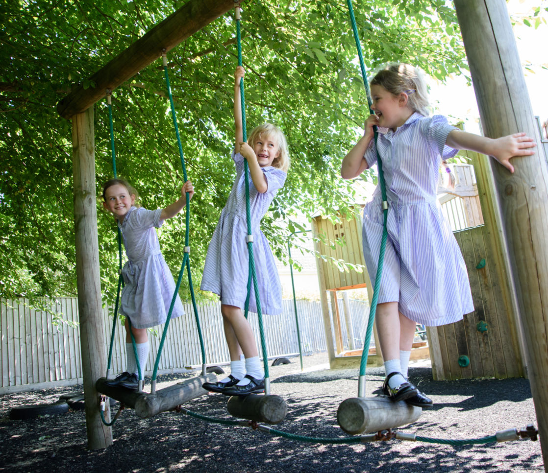 trio of wycliffe girls playing on swings