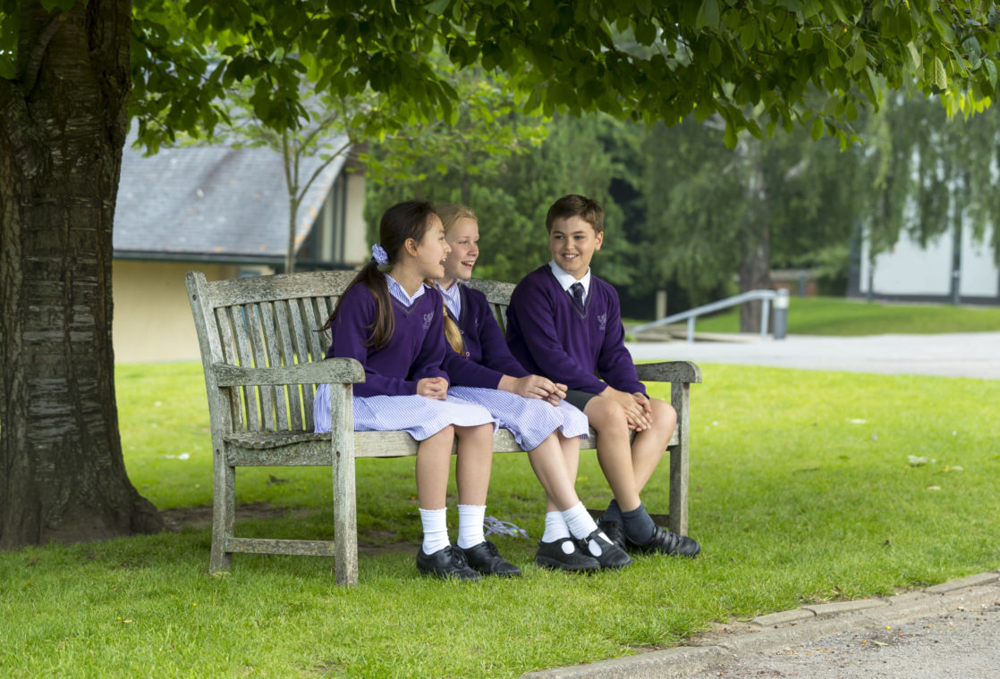 wycliffe kids sitting on a bench outdoors