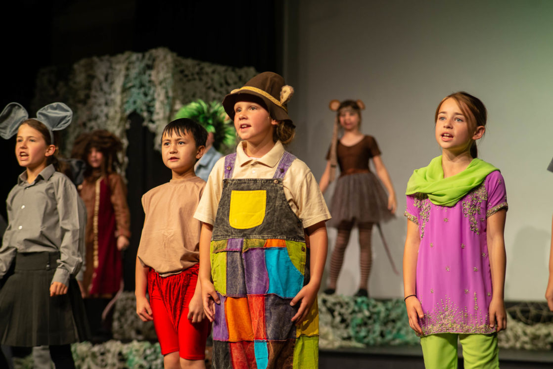 wycliffe kids wearing costumes on stage