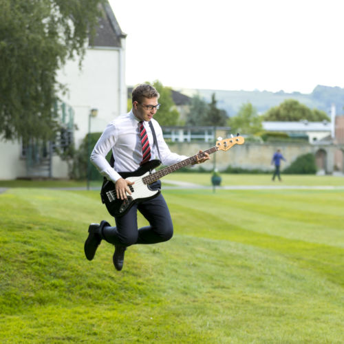 wycliffe student playing the guitar while jumping