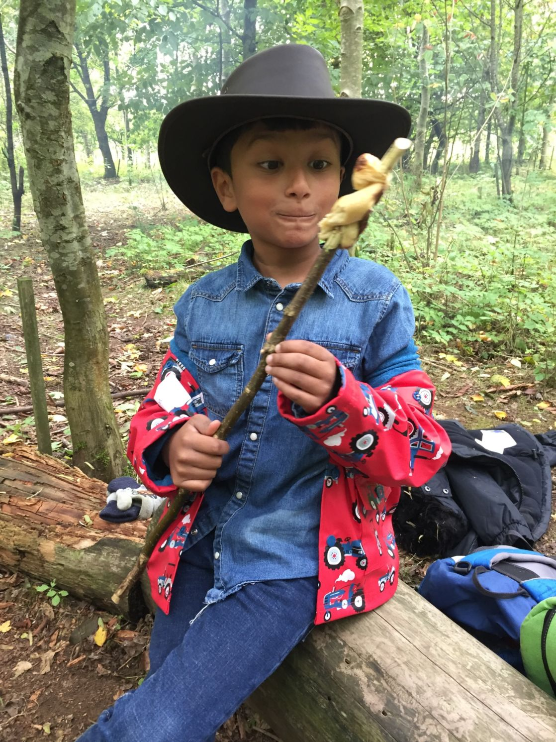 wycliffe boy in the woods holding a stick