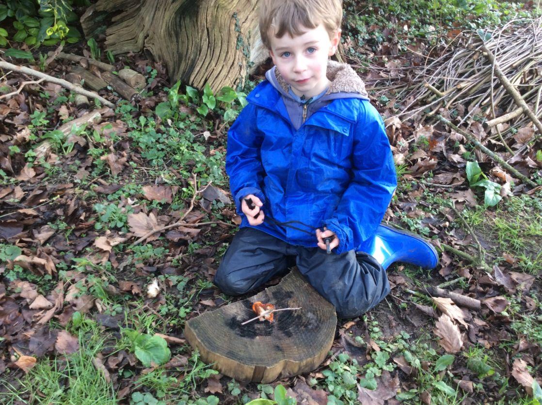 wycliffe boy in forest school making a fire