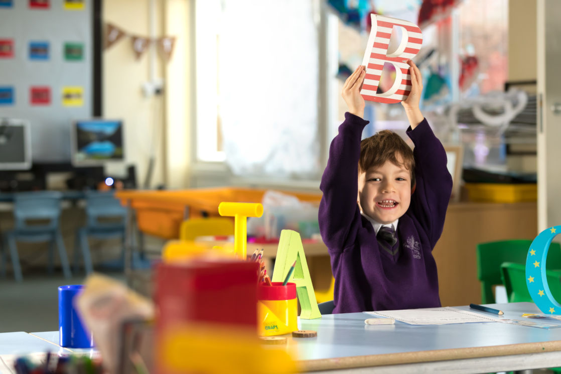 wycliffe nursery boy holding a wooden letter