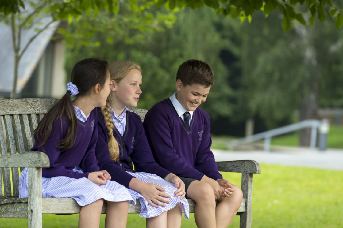 wycliffe pupils sitting on a bench outside