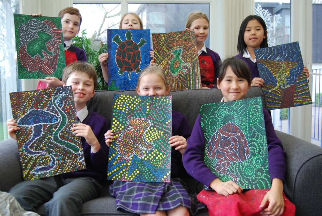 group of wycliffe students holding their paintings