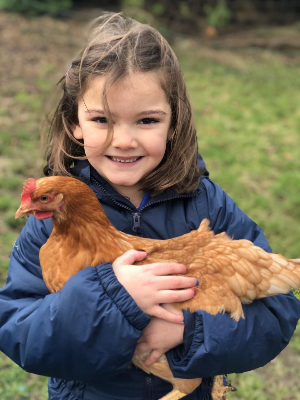 wycliffe girl hugging a hen