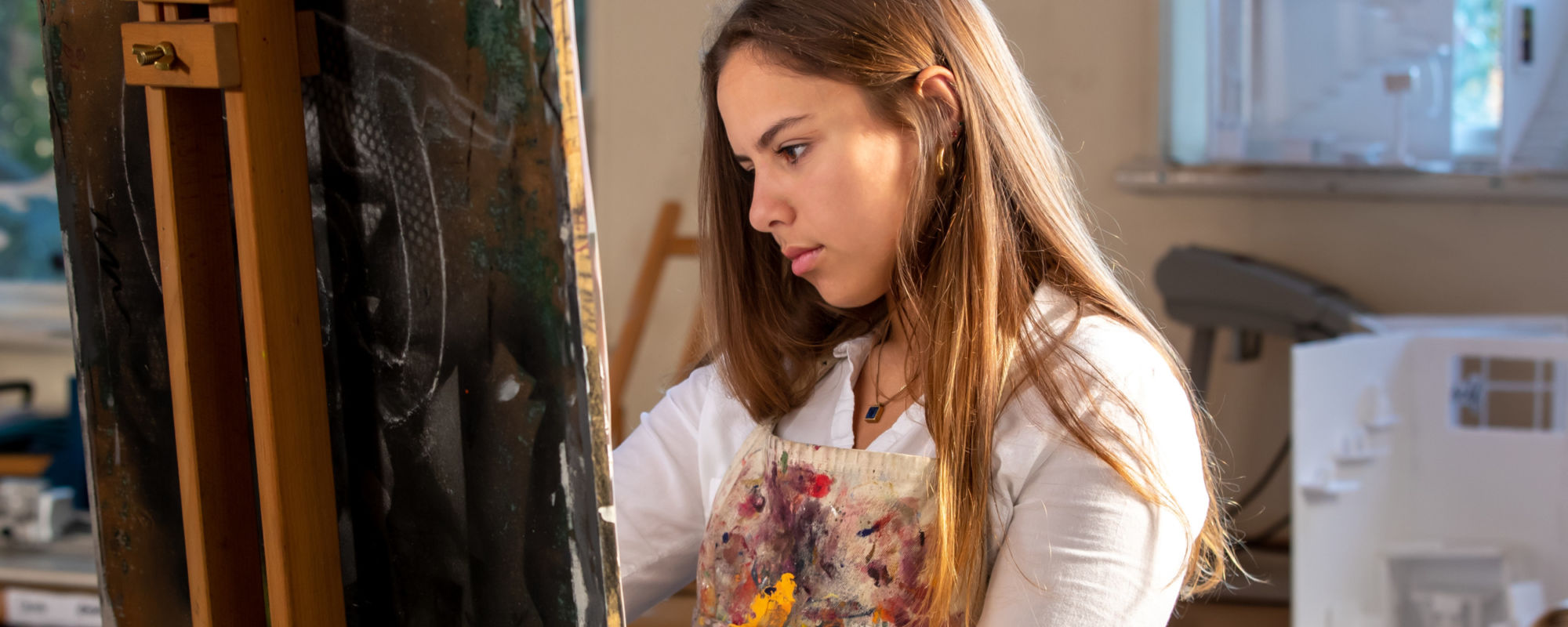 Wycliffe College student painting a piece of art