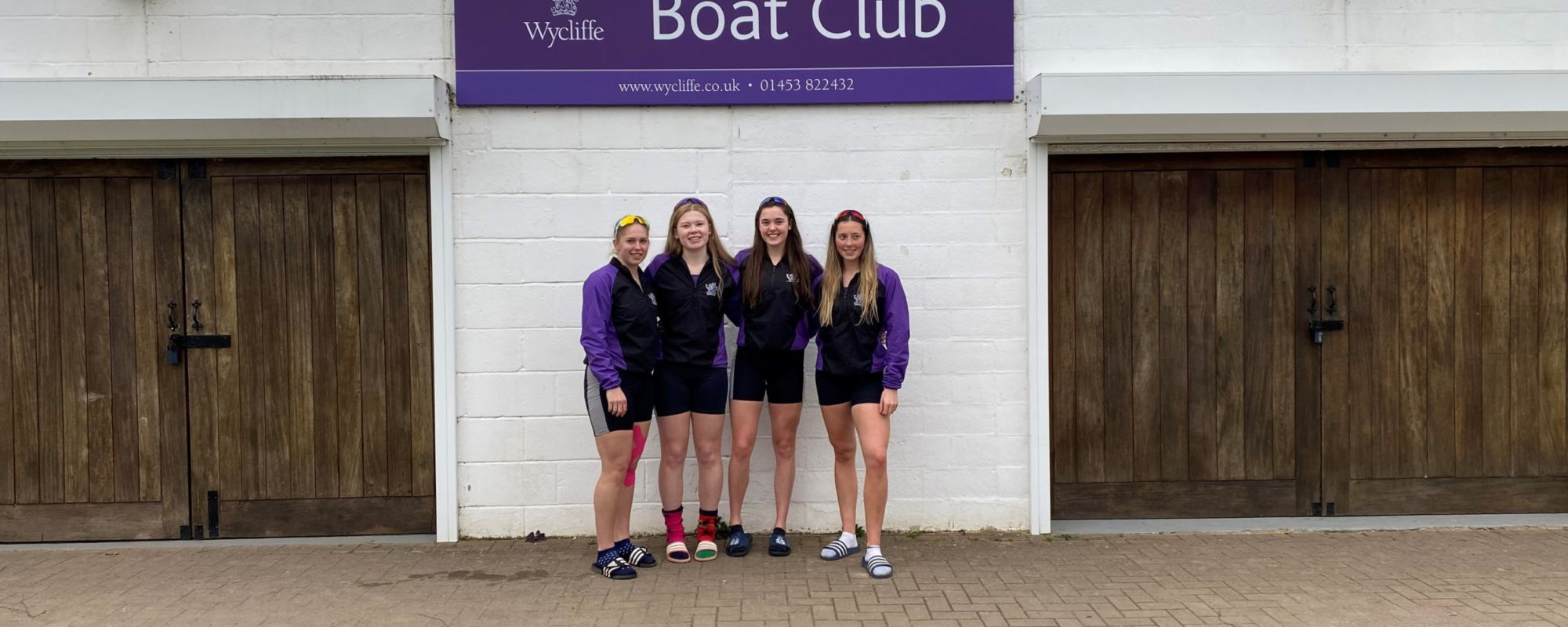 wycliffe college rowers standing outside boat club